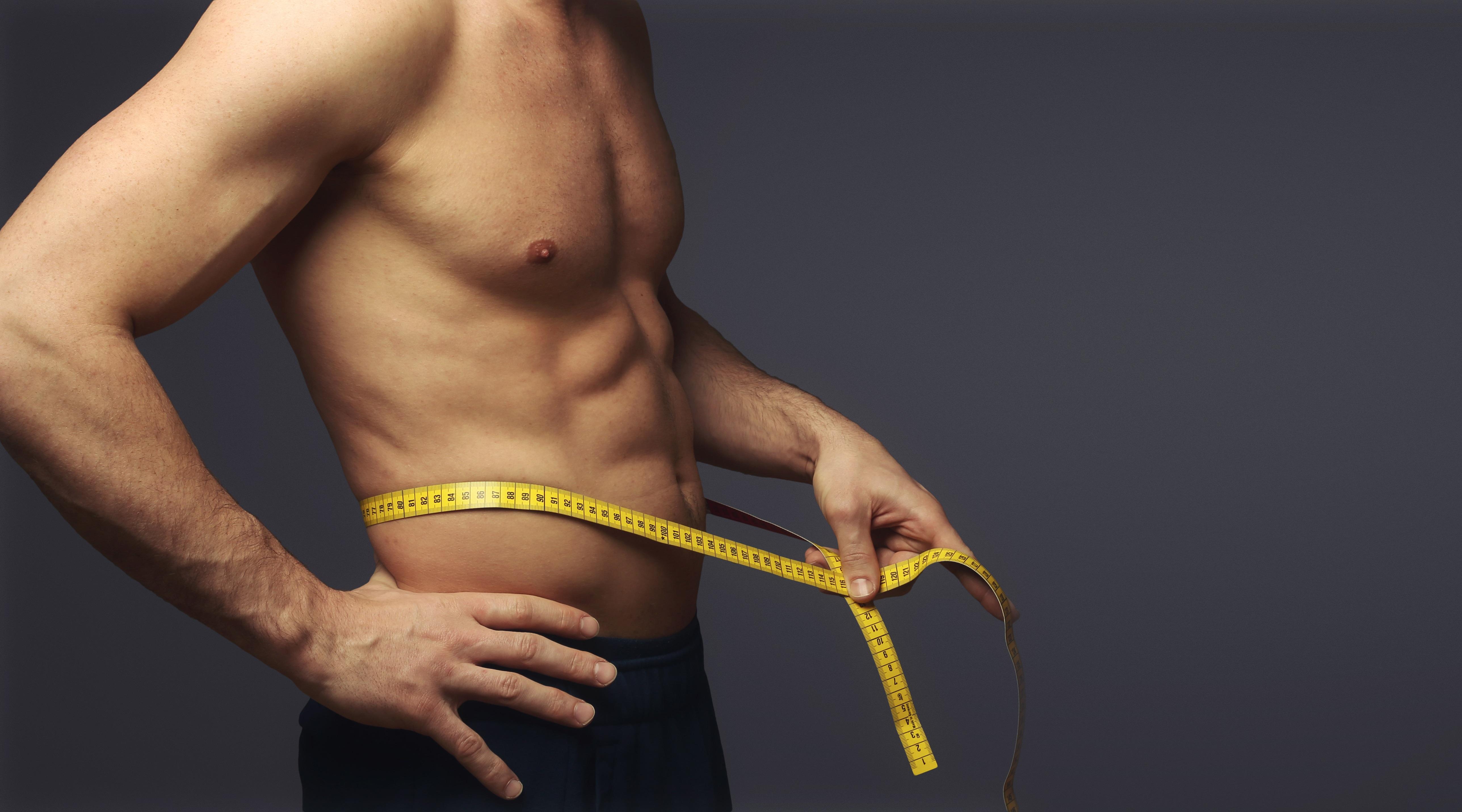 Muskulöser Mann mit Maßband um den Bauch | Dein Personal Trainer Berlin