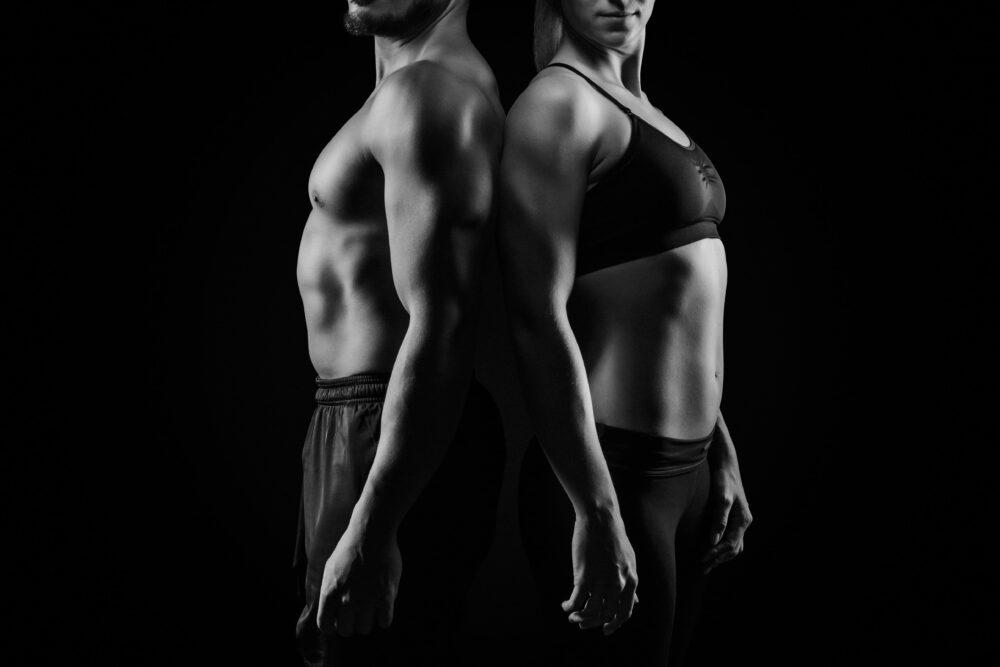 Muskulöser Mann und Frau die Rücken an Rücken in Sportkleidung stehen   Dein Personal Trainer Berlin