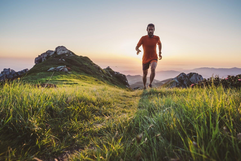 Läufer in den Bergen bei Sonnenaufgang | Dein Personal Trainer Berlin