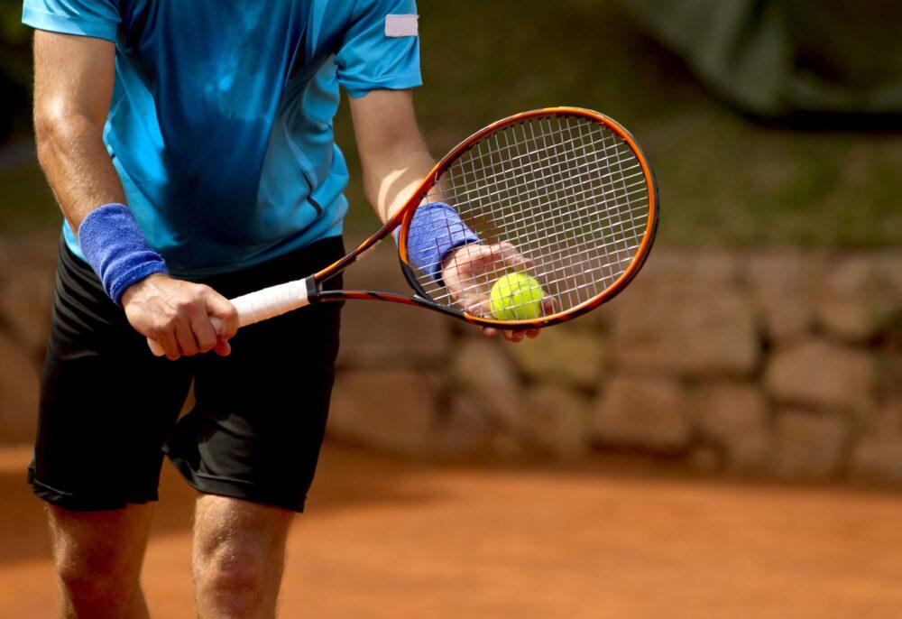 Mann macht einen Aufschlag bei einem Tennisspiel | Dein Personal Trainer Berlin