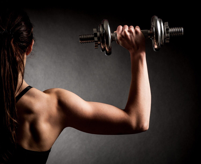 Muskuläre Frau hält eine Gewichtshantel in der Hand | Dein Personal Trainer Berlin