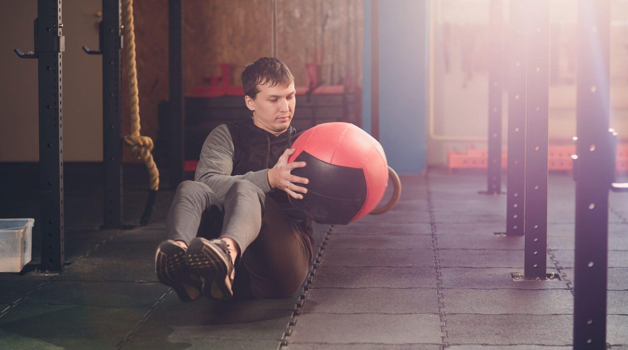 Mann beim Training mit einem Medizinball | Dein Personal Trainer Berlin
