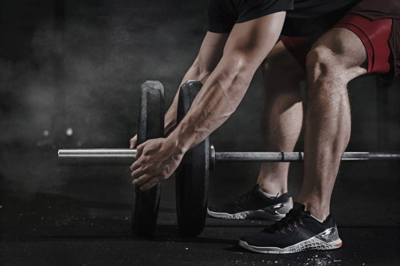 Mann macht Gewichte auf eine Gewichtsstange | Dein Personal Trainer Berlin