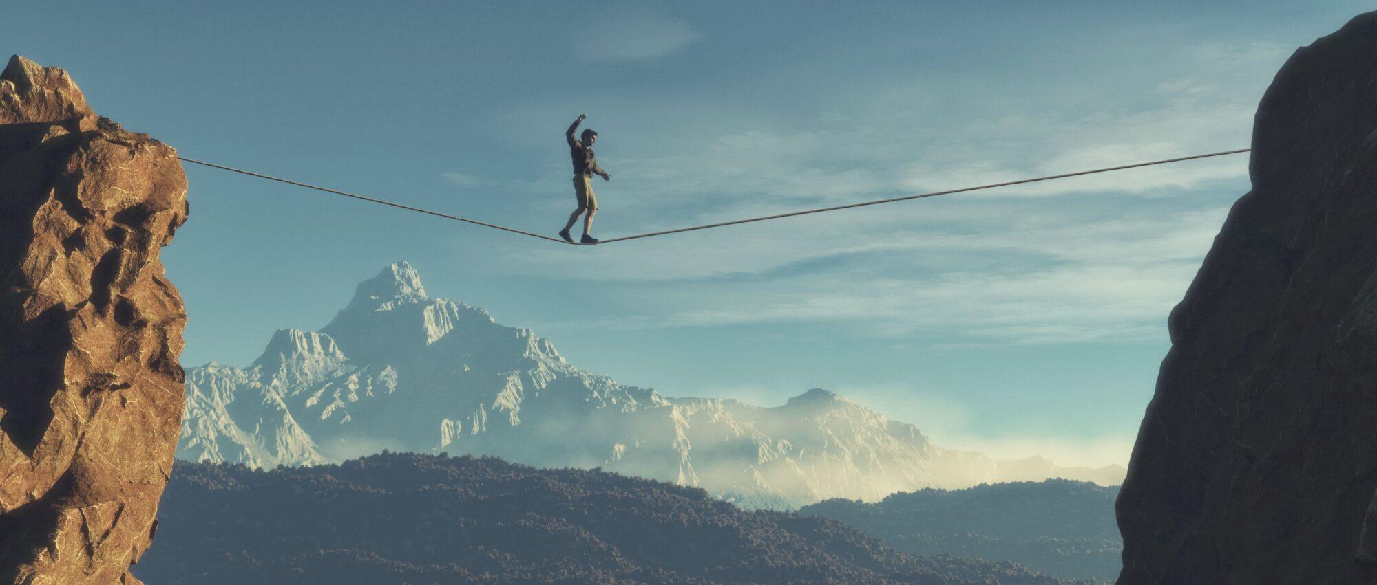 Mann läuft über ein Seil welches zwischen zwei Bergen gespannt ist | Dein Personal Trainer Berlin