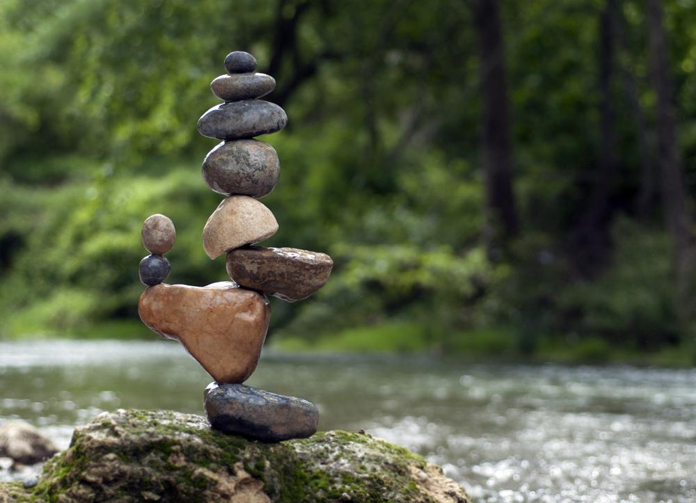 Steine die auf einander balancieren am Fluss | Dein Personal Trainer Berlin