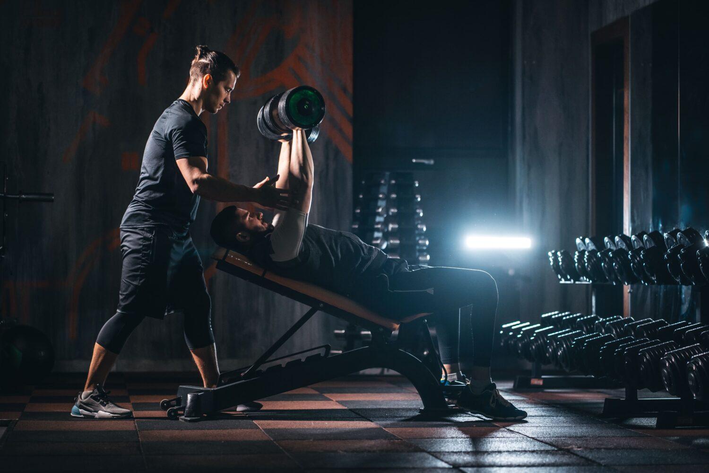 Trainer hilft Mann beim Gewichtheben mit Hanteln   Dein Personal Trainer Berlin