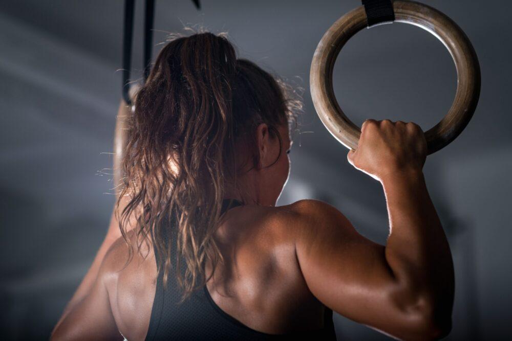 Frau die Training an Ringen macht   Dein Personal Trainer Berlin